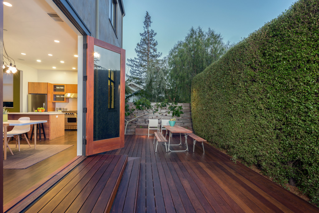 Open french doors leading into contemporary home with wooden terrace