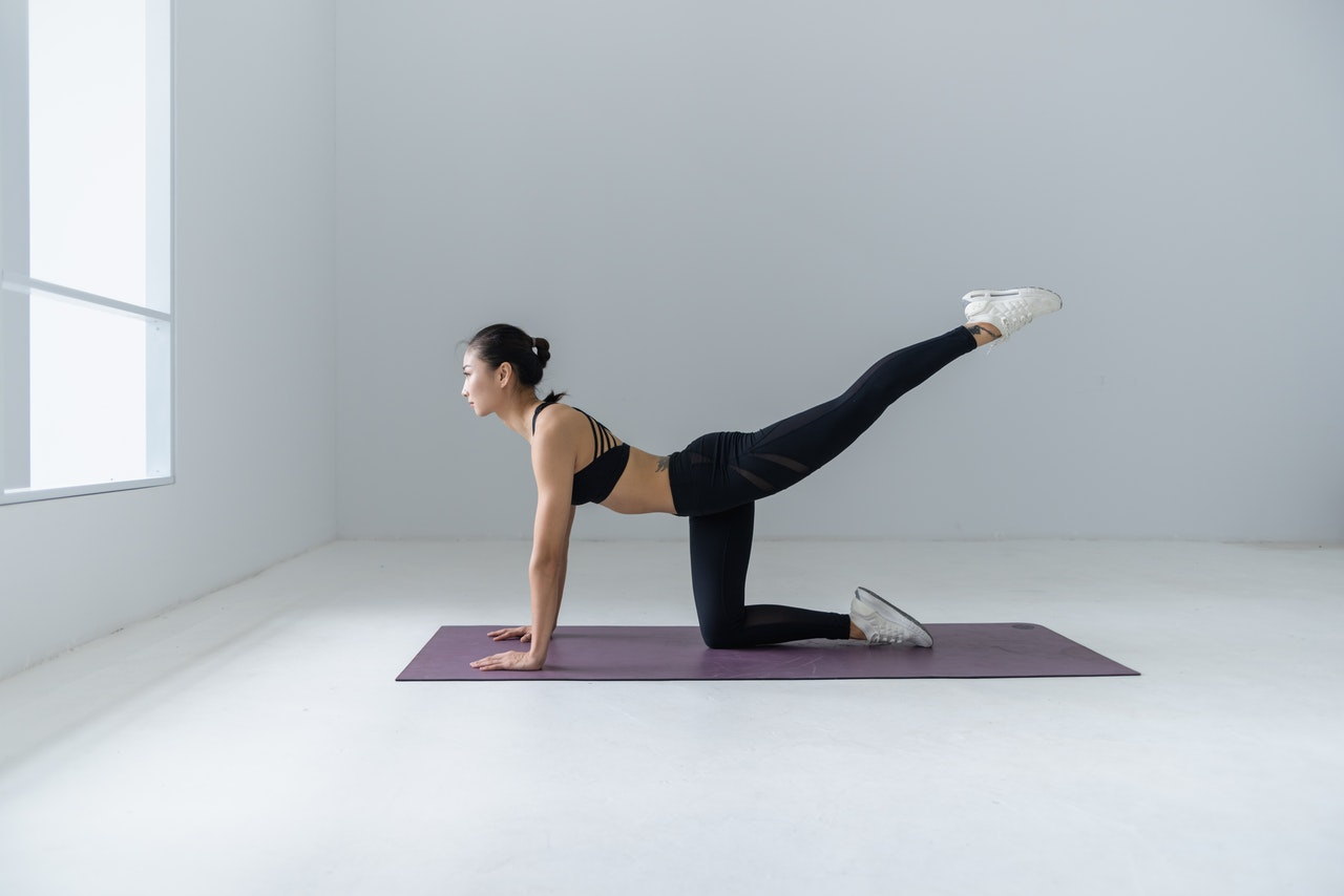 woman stretching doing yoga at home