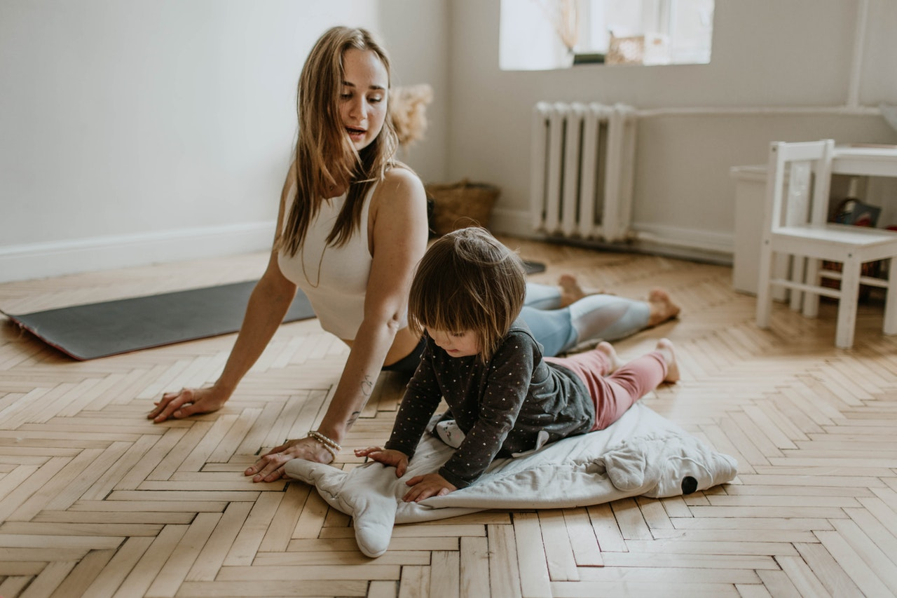 woman and her daughter stretching at home