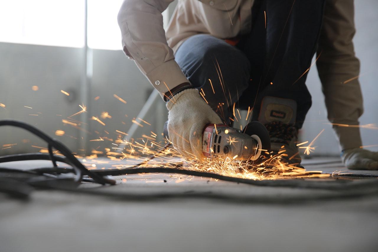 man cutting steel